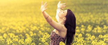 Intuition nutzen lernen: Junge Frau streckt Arme gen Himmel